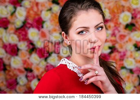 Young beautiful brunette woman has put forefinger to lips as sign of silence in a studio on a floral wall background