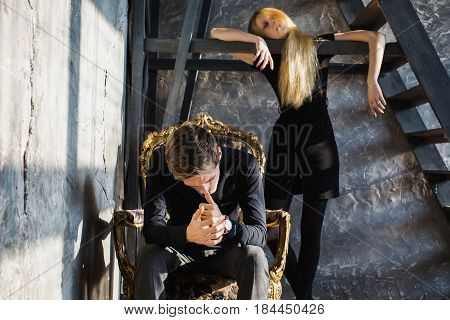 A young upset man and young blonde upset woman with long hair. Problems and difficulties in relations. Difficult situation in life. Conceptual photography.  Upset actor play. Hard shadows. Show feelings. Hide feelings.