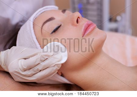 The Doctor Cosmetologist Cleanses With A Tonic The Face Skin Of A Beautiful, Young Woman In A Beauty
