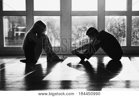 A young sad boy and sad girl with long blond hair standing in front of the window. Dancers during a workout. Problems and difficulties in relations. The difficult situation in life. Conceptual sad photography. Sad model