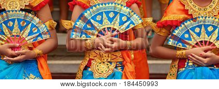 Asian travel background. Group of beautiful Balinese dancer women in traditional Sarong costumes with fans in hands dancing Legong dance. Arts culture of Indonesian people Bali island festivals.