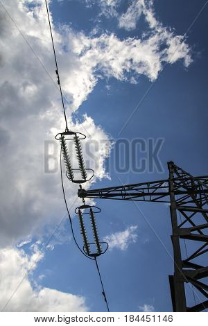 High-voltage pole of a power transmission with tensioned wires against a blue sky background