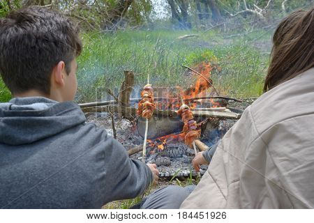 Teenagers enjoying together barbecue outdoors