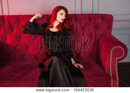 Beautiful mysterious girl with red hair and natural make-up and pale skin. A mysterious woman in a black retro dress sitting on a red couch. Model posing in studio. The unusual appearance. Insidious wicked witch mysterious woman.