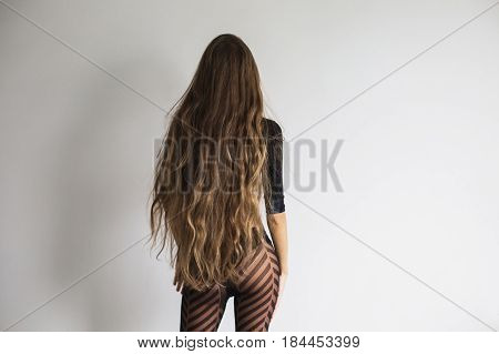 A woman is standing back with long hair. Beautiful ass in black lingerie and long hair. Nice hair. Hair concept