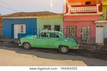 Green car on the front of green house  in the UNESCO World Heritage city center of Trinidad Cuba.