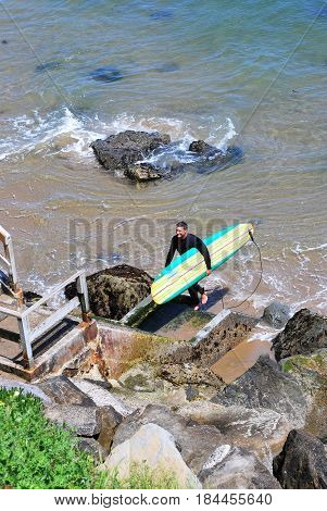 APRIL 23, 2017. SANTA CRUZ, CA.  CIRCA:  Male surfer leaving water climbing stairs to the top of the beach.