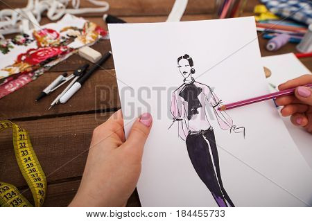 Fashion designer's hands drawing new models of female outfits on the wooden background