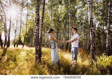 Beautiful couple. Girl with dark hair and brown eyes with a wreath on head in summer dress hugging a man in awhite shirt on a green background. Loving couple in the forest on a sunny day. Couple love each other. Nice couple