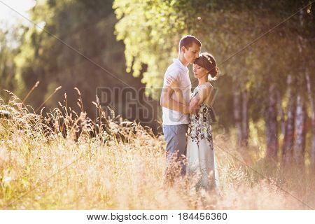 Beautiful couple. Couple in forest. Girl with dark hair and brown eyes with a wreath on head in summer dress hugging a man in awhite shirt on a green background. Loving couple in the forest on a sunny day. Couple love each other. Nice couple