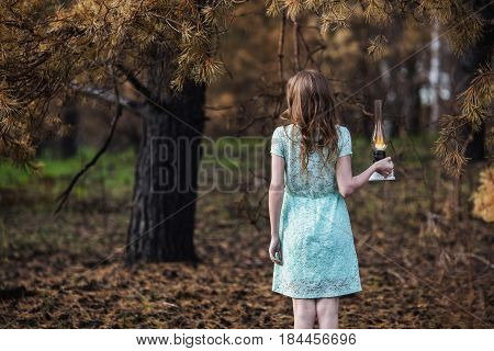 Very cute young girl with a kerosene lamp. Doll appearance. Woman with brown hair in a turquoise dress on nature with lamp. Long hair. Natural light. Model posing on the nature. Lamp in hand. Lost in forest