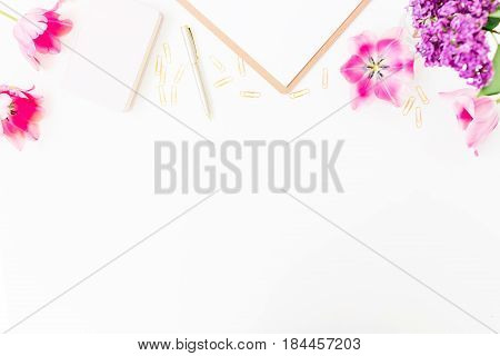 Beauty blog concept. Freelancer or blogger workspace with clipboard, notebook, tulip flowers and accessories on white background. Flat lay, top view.