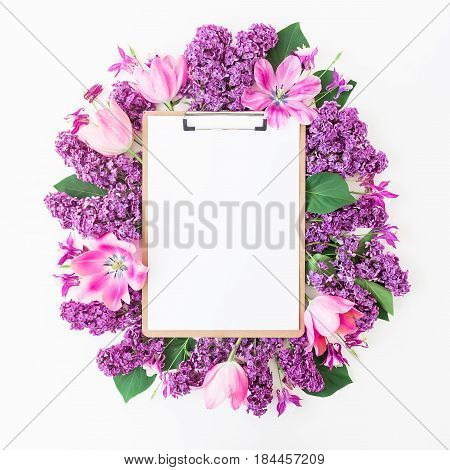 Clipboard, lilac branches and tilips on pink background. Flat lay, top view. Beauty blog concept.