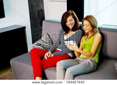 Mother and daughter sitting in living room. Chill time.