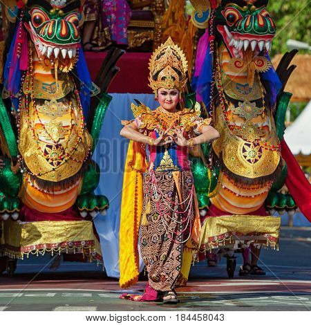 DENPASAR BALI ISLAND INDONESIA - JUNE 11 2016: Beautiful woman dancer in bright traditional costume on dragon mask backgroung. Balinese people dancing on street parade at art and culture festival.