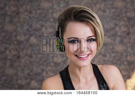 Lovely joyful girl with tanned skin and white hair listening to music on headphones. Female beauty joyful portrait of a beautiful makeup. Enjoying good music. Joyful model. Joyful music