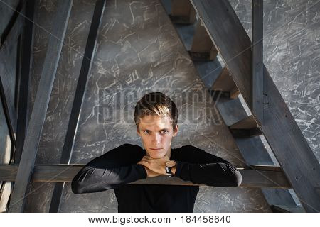 A young dramatic guy in a black shirt with a clock on the hand in the dark room with natural light. Emotional dramatic portrait. Bright display of emotion. Conceptual dramatic photography. The talented dramatic actor.
