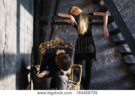 A young man and young blonde woman with long hair. Problems and difficulties, conflict in relations. Difficult conflict situation in life. Conceptual photography. Actor play conflict. Hard shadows. Show feelings. Hide feelings in conflict.