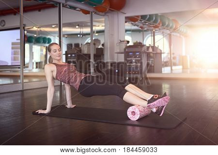 Woman in sleeveless shirt and black leggings in gym doing exercise with foam or fascia roll and looking at camera