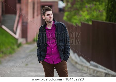 Young handsome attractive cheerful man with dark hair with a beard wearing a shirt and a black jacket on the street. Male handsome street style. Nature in spring. Walking around the city. Handsome guy