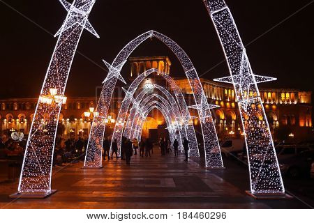 YEREVAN, ARMENIA - JAN 5, 2017: Arcade with illumination at Republic Square, walking people at night
