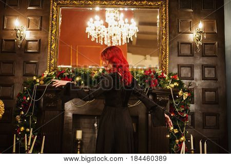 Beautiful girl with red hair and natural make-up and pale skin. A woman in a black retro dress. Model posing on the background of the fireplace. The unusual appearance. Insidious wicked witch woman.