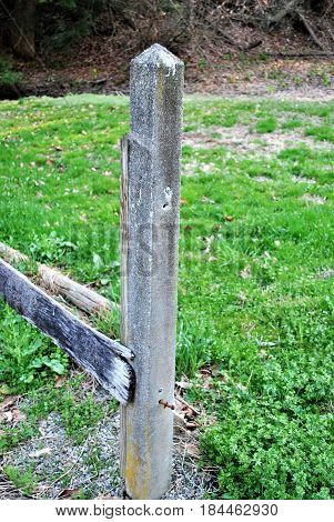 A fence being fixed with cement posts.