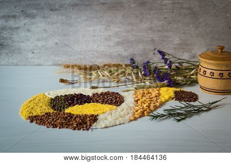 Placer of grains and cereals in form of horn of plenty on a white background.