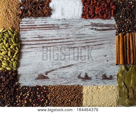 Spices frame with copy space for creativity. Black pepper, cardamom, coriander, mustard seeds, bay leaf, cinnamon, anise, goji berries, salt, sesame and cloves.