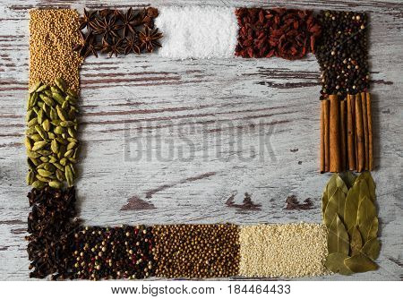 Copy space of spices frame. Black pepper, cardamom, coriander, mustard seeds, bay leaf, cinnamon, anise, goji berries, salt, sesame and cloves on a gray background.