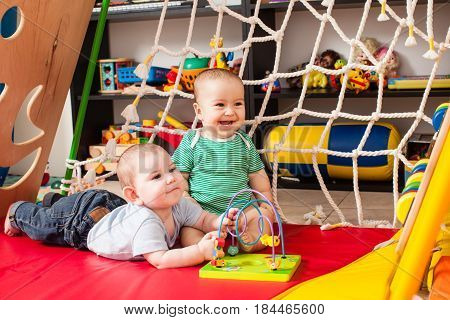 Two clever boy babies playing with toy in playroom