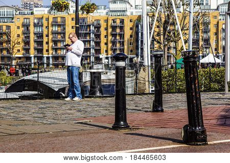 LONDON , ENGLAN -1 April 2017 : An unidentified man uses the handset to keep in touch with other people. The mobile phone is the device used to call, write, and surf the Internet more widespread in the world