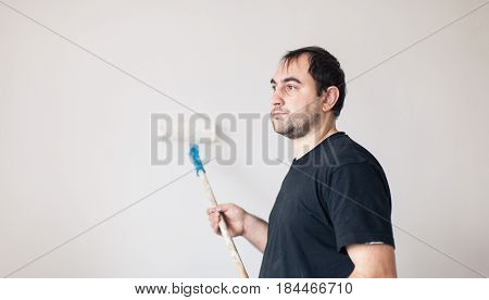 Side view of a man with roller painting a wall in white