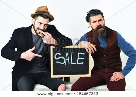 Two bearded mens short and long beard. Caucasian stylish hipsters with moustache holding sale inscription on blackboard and smoking cigars isolated on white background