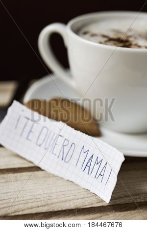 closeup of a piece of paper with the text te quiero mama, I love you mom written in spanish, next to a cup with cappuccino