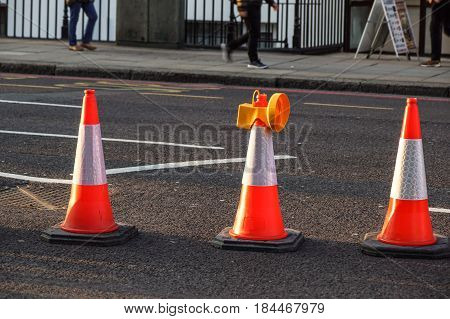 traffic cone, with white on gray asphalt, at roadwork.