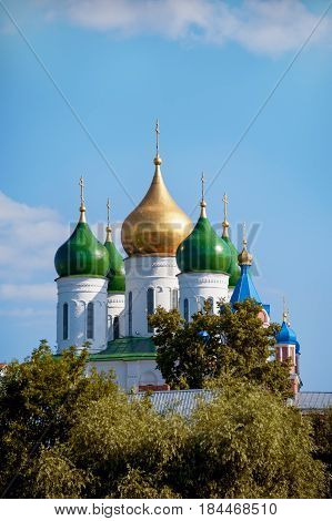 Kolomna domes of the assumption Cathedral on the Cathedral square among the trees on a Sunny summer day with clouds in the sky