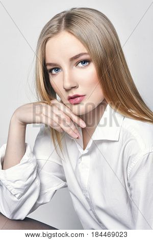 Beautiful sexy blond woman. Girl with perfect body sitting on the stool. Beautiful long hair and legs smooth clean skin skin care and hair. Delicate romantic look