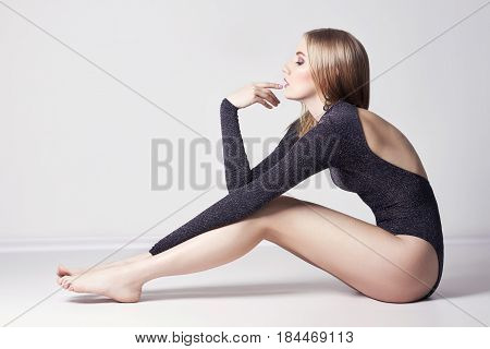 Beautiful sexy blond woman. Girl with perfect body sitting on the floor. Beautiful long hair and legs smooth clean skin skin care and hair. Delicate romantic look