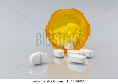 Pills spilling from an open bottle on white backgroubd