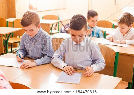 Boy white in the copybook during the lesson of primary school