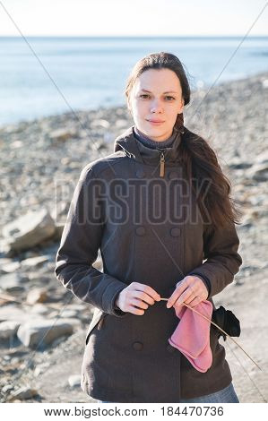 Beautiful young happy woman portrait against seascape, long hair fluttering in the wind.