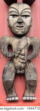 Auckland New Zealand - March 2 2017: Closeup of Te Hawiti Ancestor wood sculpture on totem pole in front of Arataki Maori Heritage Center. Brown wood of naked man on scarlet background.
