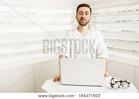 Male optometrist consultant, standing in the workplace, at ophthalmic clinic. In the background a showcase with a many glasses