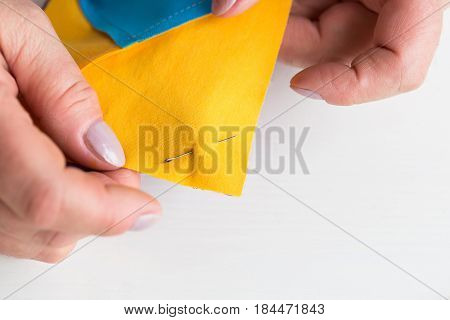 needlework and quilting at the workshop of a tailor woman on white background - close-up on the fingers of tailor fastened with the safety pin scraps of blue and yellow fabric for patchwor