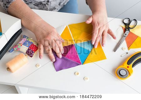 needlework and quilting in the workshop of a tailor woman on white background - tailor at work with pieces of colored cloth on the table with threads, fabrics, needles, sewing machine, rotary cutters