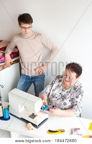 patchwork and quilting - woman tailor prepares cutting colored pieces of fabric for sewing machines, the young man is watching her work, on the table threads, pads, pins, buttons and cutters