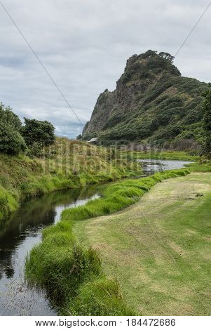 Auckland New Zealand - March 2 2017: Creek between Karekare Waterfall and Karekare beach flows between green lawn and wild area. Forested hill and cloudscape over beach.