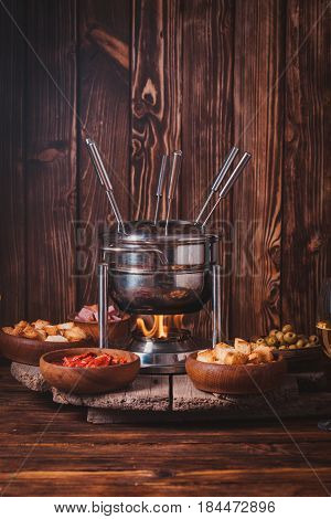 Delicious Cheese Fondue on a fork on a wooden stand