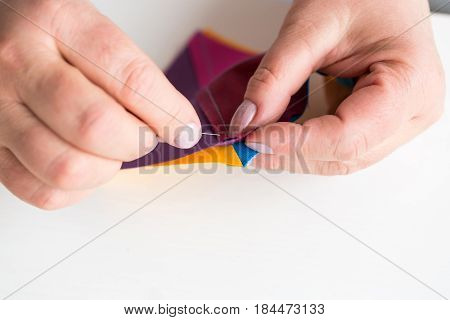 needlework and quilting in the workshop of a tailor woman on white background - close-up on the tailor hand sewing by a needle scraps of colored fabric for patchwork